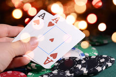 Casino chips and pair of aces in a croupier's hand against bright bokeh lights. Poker game theme concept. Stock Photos