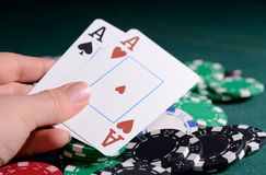 Casino chips and pair of aces in a woman's hand. Poker game concept Royalty Free Stock Image