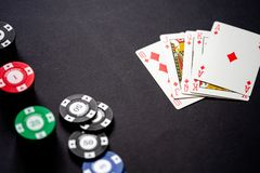 Casino chips and playing cards on minimalistic black background. Royal flash stock photography