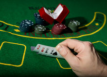 Casino chips and a precious ring on green poker table background, man holding losing combination of cards Stock Image