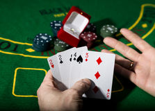 Casino chips and a precious ring on green poker table background, man holding losing combination of cards Royalty Free Stock Photos