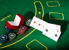 Casino chips and a precious ring on green poker table background, man throws cards with losing combination. Royalty Free Stock Photography