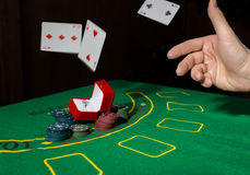 Casino chips and a precious ring on green poker table background, man throws cards with losing combination. Stock Photography