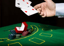 Casino chips and a precious ring on green poker table background, man throws cards with losing combination. Royalty Free Stock Photo