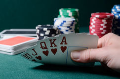 Casino chips and royal flush cards combination on the green table. Poker game theme Royalty Free Stock Images
