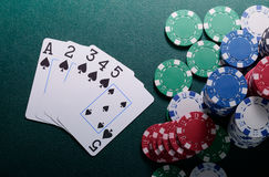 Casino chips and straight cards combination on the green table. Poker game concept Royalty Free Stock Photography