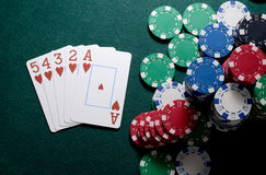Casino chips and straight flush cards combination on the green table. Poker game concept Royalty Free Stock Photography