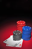 Casino chips with two aces. Several stacks of casino chips of various heights and colors with two aces, a black and a red one, all sitting on a red colored royalty free stock photography