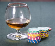 Casino: Cognac, playing-cards. Glass with cognac and chips for a game in a casino Stock Images
