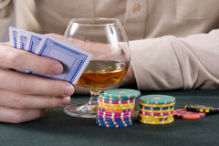 Casino: Cognac, playing-cards and chips. Glass with cognac and chips for a game in a casino Stock Photo