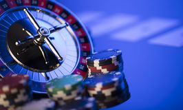 Casino concept. Place for typography. High contrast image of casino roulette, poker chips. Blue light and place for text royalty free stock photos
