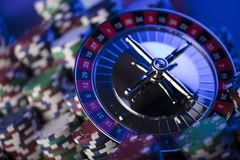 Casino concept. Place for typography. High contrast image of casino roulette, poker chips. Blue light and place for text stock photography