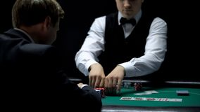 Casino croupier giving businessman all chips for winning at poker, gambling. Stock photo stock image
