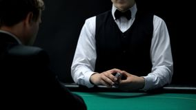 Casino croupier holding deck of cards on green table for client, poker game. Stock photo royalty free stock photography