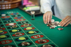 Casino. A croupier is placing chips on the table Stock Image