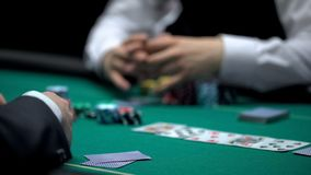 Casino croupier waiting for poker player to reveal cards combination, gambling. Stock photo stock images