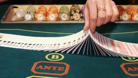 Casino: De handelaar schuifelt de pookkaarten stock videobeelden