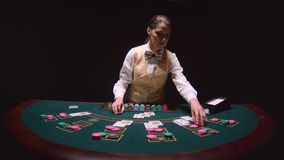 Casino dealer autopsy of the three cards on the flop, playing poker on the green table. Black background. Slow motion. Casino dealer woman autopsy of the three stock video footage