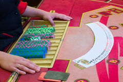 Casino dealer (croupier) spreaded the deck of cards on the Poker table Royalty Free Stock Photo