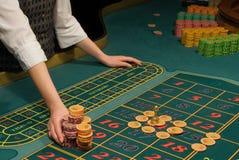 Casino dealer handling a big pile of chips Stock Photos