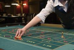 Casino dealer handling gambling chips Royalty Free Stock Images