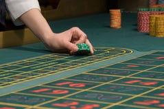 Casino dealer handling gambling chips Royalty Free Stock Photos