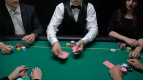 Casino dealer shuffling and distributing cards, players checking combination