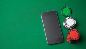 Casino del teléfono móvil en línea Teléfono móvil y microprocesadores en la tabla de juego verde Apego de juego en juegos que se  imagen de archivo