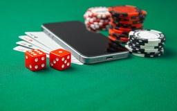 Casino del teléfono móvil en línea Teléfono móvil y tarjetas de juego con los microprocesadores y dados en una tabla de juego ver imagen de archivo libre de regalías