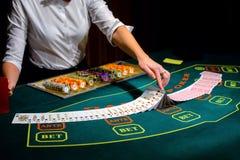 Casino: El distribuidor autorizado mezcla las tarjetas del póker imágenes de archivo libres de regalías