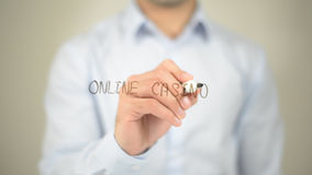 Casino en línea, escritura del hombre en la pantalla transparente foto de archivo