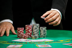 Casino gambling chips. Blackjack In a Casino, A Man Makes A Bet, And Puts A Chip Royalty Free Stock Images