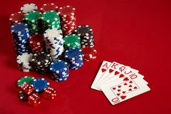 Casino gambling poker equipment and entertainment concept - close up of playing cards and chips at red background. Royal. Flush heart. Casino background. Copy Stock Photos