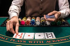 Close up of holdem dealer with playing cards and chips on green table. Casino, gambling, poker, people and entertainment concept - close up of holdem dealer with Royalty Free Stock Photography