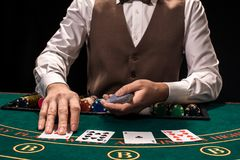 Close up of holdem dealer with playing cards and chips on green table. Casino, gambling, poker, people and entertainment concept - close up of holdem dealer with Royalty Free Stock Images