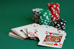 Casino Games. Four piles of casino tokens and a deck of cards on a green table Royalty Free Stock Photography
