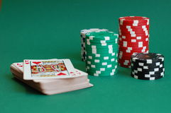 Casino Games. Four piles of casino tokens and a deck of cards on a green table Stock Photography