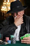 Casino guy. Mafia type with leather jacket playing poker in a classy casino Royalty Free Stock Photo