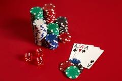 Casino het gokken van het pookmateriaal en vermaak concept - sluit omhoog van speelkaarten en spaanders bij rode achtergrond drie stock foto's