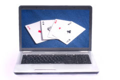 Casino internet pokersite pc. Computer laptop with four casino poker playing cards on screen Royalty Free Stock Photography
