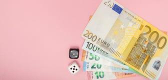 Casino, jugando y concepto de la fortuna - cercano para arriba del dinero blanco y negro de los dados y del euro en fondo rosado  imagenes de archivo