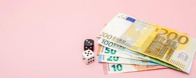 Casino, jugando y concepto de la fortuna - cercano para arriba del dinero blanco y negro de los dados y del euro en fondo rosado  imagen de archivo
