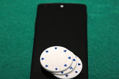 Casino in mobile phone. Poker/Casino chips on black mobile phone and green background stock images