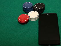 Casino on mobile phone. Poker/Casino chips near black mobile phone and green background royalty free stock image