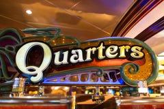 Casino Neon Quarter Sign. Interior of a cruise ship casino with a neon quarter sign over a slot machine bank Stock Photography