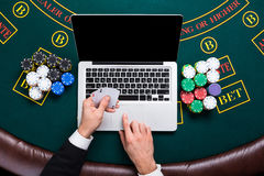 Casino, online gambling, technology and people concept - close up of poker player with playing cards Stock Photo
