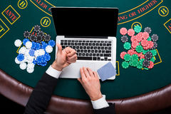 Casino, online gambling, technology and people concept - close up of poker player with playing cards Royalty Free Stock Photos