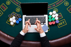 Casino, online gambling, technology and people concept - close up of poker player with playing cards Royalty Free Stock Photo