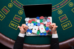 Casino, online gambling, technology and people concept - close up of poker player with playing cards Royalty Free Stock Photography
