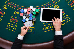 Casino, online gambling, technology and people concept - close up of poker player with playing cards Stock Image